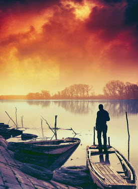 Dragan Todorovic SILHOUETTED MAN ON BOAT ON RIVER AT SUNSET Men