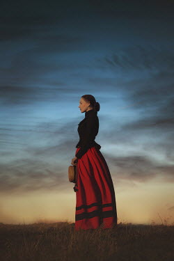 Joanna Czogala HISTORICAL WOMAN HOLDING HAT IN COUNTRYSIDE AT DUSK Women