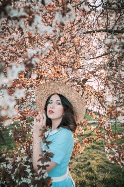 Jovana Rikalo WOMAN IN STRAW HAT BY TREE IN BLOSSOM Women