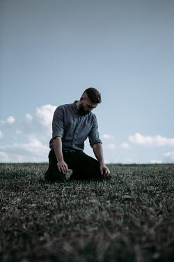 Magdalena Russocka sad man kneeling in field