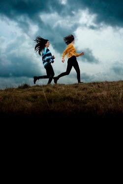 Rekha Garton TWO GIRLS RUNNING IN FIELD AT DUSK Women