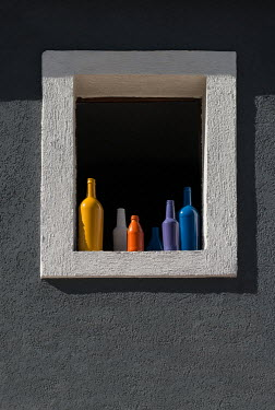 Jaroslaw Blaminsky MULTI-COLOURED BOTTLES IN WINDOW WITH SUNLIT Building Detail