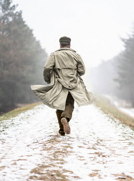 Jaroslaw Blaminsky MAN RUNNING ON SNOWY COUNTRY LANE Men