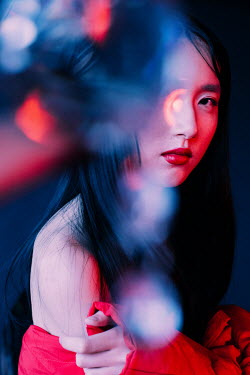 Marta Syrko CLOSE UP OF ASIAN GIRL WITH RED LIGHT Women