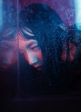 Marta Syrko CLOSE UP OF SAD ASIAN GIRL WITH WET GLASS Women
