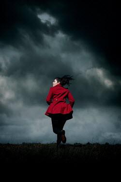 Rekha Garton WOMAN IN RED JACKET RUNNING OUTDOORS AT DUSK Women
