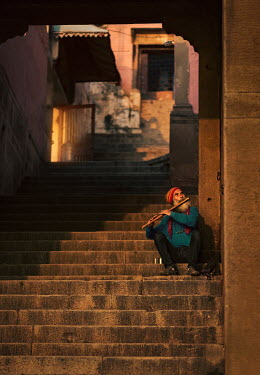 Ashraful Arefin MAN SITTING PLAYING FLUTE ON CITY STEPS Men