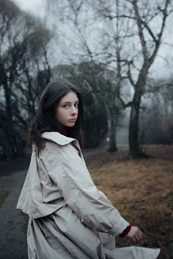 Irina Orwald Young woman in coat walking in park