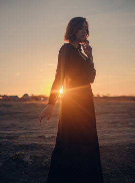 Irina Orwald Young woman in black dress standing in field at sunset