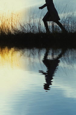 Magdalena Russocka silhouetted girl running by sunlit river Women