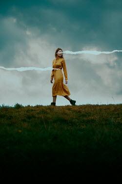 Rekha Garton Woman in yellow dress walking on hill