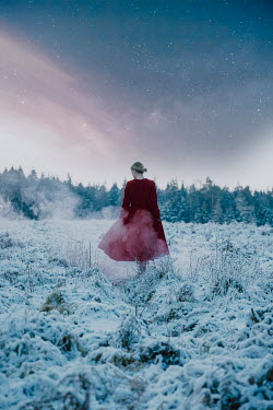 Rekha Garton Woman in red dress walking in snowy field