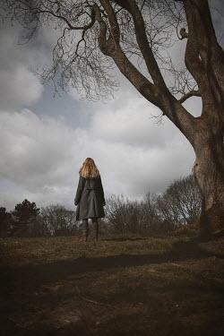 Shelley Richmond Woman in coat standing by tree