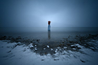 Viktoria Haack WOMAN STANDING IN SEA WITH SNOWY BEACH Women