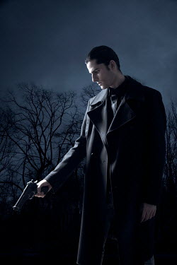 Miguel Sobreira Young man in black coat with pistol at night