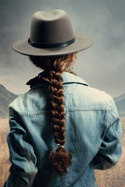 Magdalena Russocka woman in cowboy hat standing in countryside with mountains