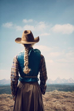 Magdalena Russocka woman in cowboy hat standing in countryside with mountainscape