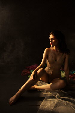 Marta Syrko Young woman in bodysuit sitting in shadow