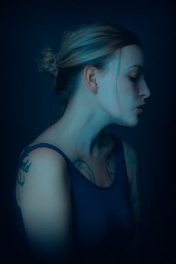 Rekha Garton Young woman with tattoos in shadow
