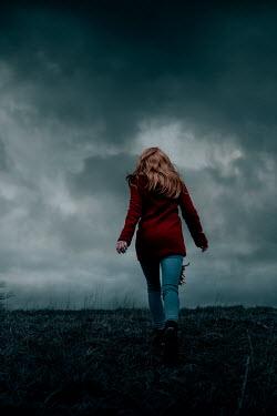 Rekha Garton Woman in red coat walking on hill