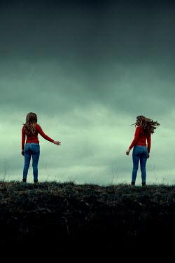 Rekha Garton Women in red sweaters standing on hill