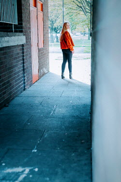 Shelley Richmond Young woman in red jacket in alleyway