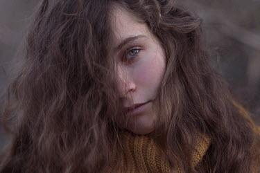 Anna Rakhvalova CLOSE UP OF SAD BRUNETTE GIRL WITH HAIR COVERING FACE Women