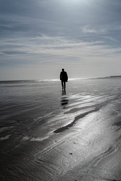 CollaborationJS SILHOUETTED MAN WALKING ON SANDY BEACH Men