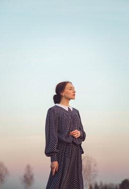 Joanna Czogala WOMAN IN POLKA DOT DRESS OUTDOORS AT SUNSET Women