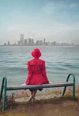 Joanna Czogala WOMAN SITTING BY WATER WITH SKYLINE Women