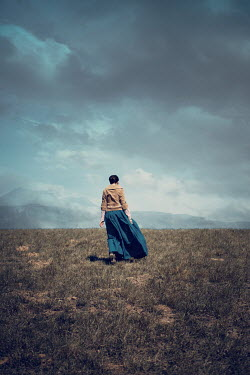 Magdalena Russocka historical woman walking in field with mountainsacape
