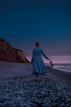 Rekha Garton WOMAN CARRYING LAMP ON BEACH AT DUSK Women