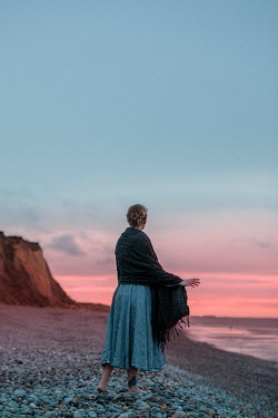 Rekha Garton WOMAN WITH SHAWL STANDING ON BEACH AT SUNSET Women