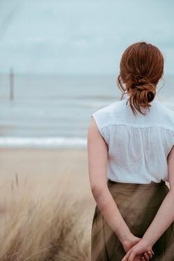 Rekha Garton WOMAN WITH RED HAIR ON BEACH WATCHING SEA Women