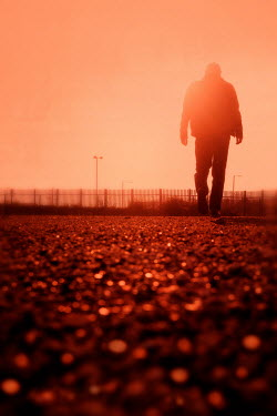 Tim Robinson SILHOUETTED MAN WALKING ON ROAD AT SUNSET Men