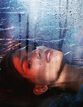 Marta Syrko BRUNETTE WOMAN LYING BEHIND WET WINDOW Women