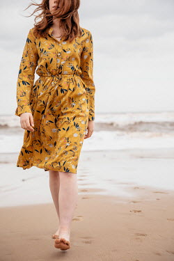 Rekha Garton WOMAN IN FLORAL DRESS WALKING ON SANDY BEACH Women