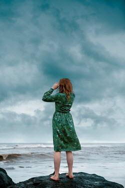 Rekha Garton WOMAN WITH RED HAIR ON ROCK WATCHING SEA Women