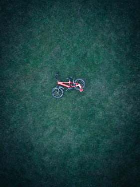 Magdalena Russocka aerial view of child's tricycle lying on grass