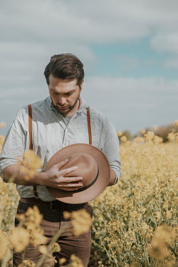 Rekha Garton SAD MAN HOLDING HAT IN SUMMERY FIELD Men