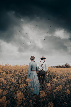 Rekha Garton COUPLE WALKING IN FIELD WITH STORMY SKY Couples