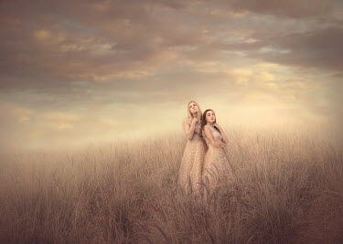 Jessica Drossin TWO GIRLS IN PINK DRESSES STANDING IN FIELD Women