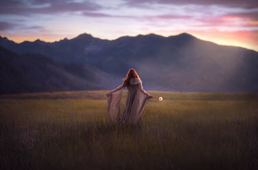 Jessica Drossin WOMAN WITH FLOWER WATCHING MOUNTAINS AT SUNSET Women