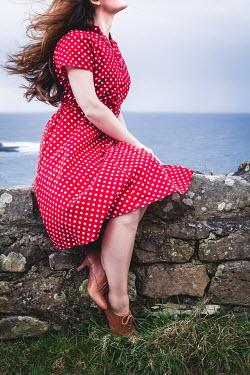 Marie Carr WOMAN IN RED SPOTTY DRESS SITTING ON WALL BY SEA Women
