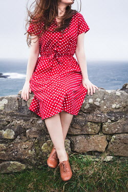 Marie Carr WOMAN IN RED SPOTTY DRESS SITTING ON WALL BY SEA Women