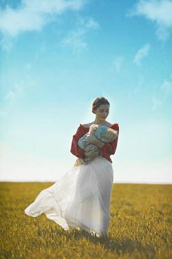 Ildiko Neer Historical woman holding baby on field