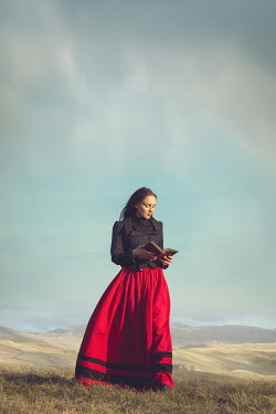 Joanna Czogala Young woman in red Victorian skirt standing on hill