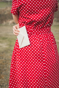 Marie Carr Young woman in 1940s spotted red dress holding envelope