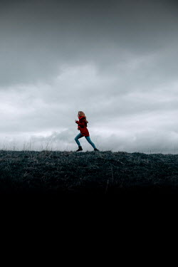 Rekha Garton Young woman in red coat running on hill