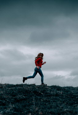 Rekha Garton Young woman in red sweater running on hill